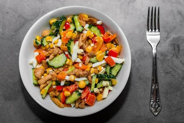 Salade de légumes lumineux au poulet sur fond de béton gris