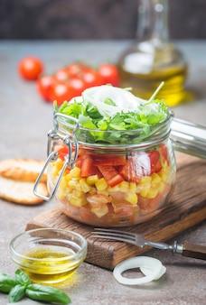 Salade de légumes maison saine mason jar avec tomates, maïs, poivron, roquette et oignon