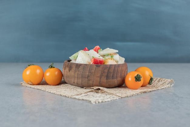 Salade de légumes mélangés dans une tasse en bois sur la table en béton.