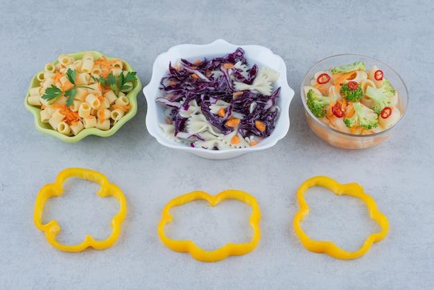 Salade de légumes sur plaque blanche avec macaroni sur surface en marbre