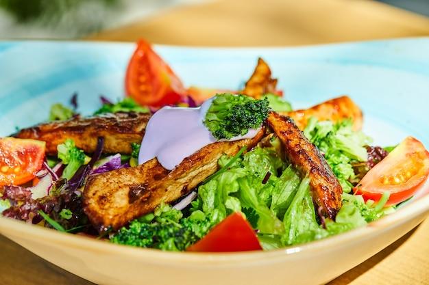 Salade de légumes et poulet sur plaque bleue