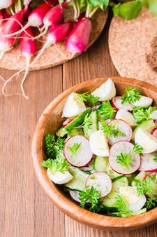 Salade de légumes de printemps dans une assiette en bois