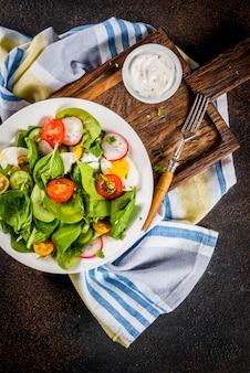 Salade de légumes de printemps frais, fond de béton foncé au-dessus