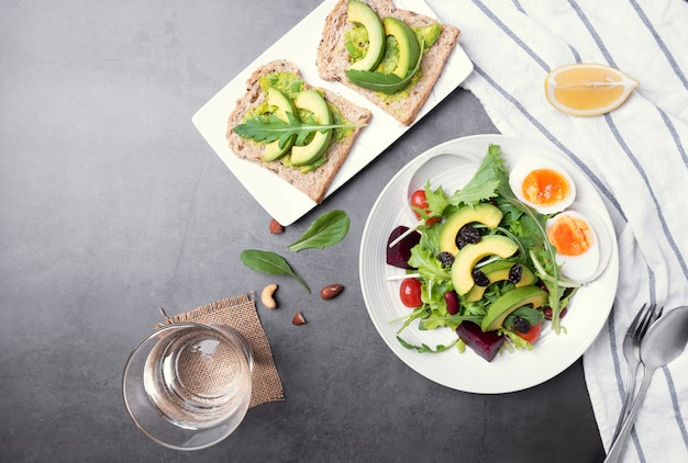 Salade de légumes sains frais avec oeuf, tomate, avocat, épinards, laitue dans l'assiette sur fond de tableau.
