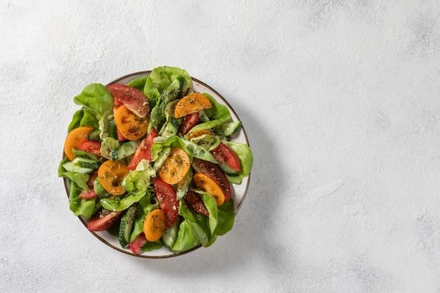 Salade de légumes sains de légumes frais de tomates, concombres, oignons, épinards, laitue sur une assiette. menu de régime. vue d'en-haut.