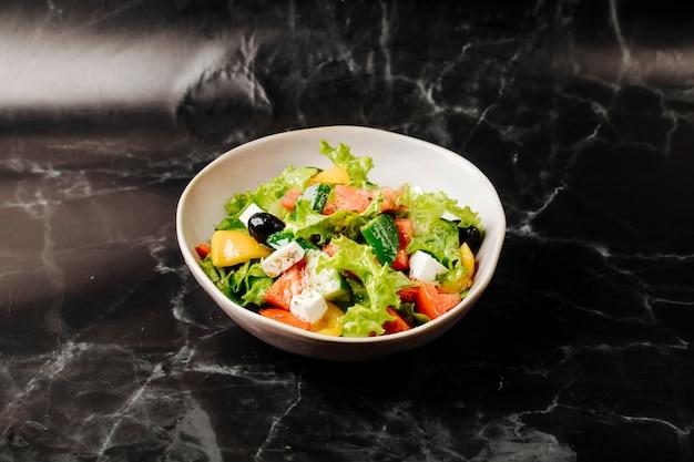 Salade de légumes de saison avec des aliments mélangés dans un bol blanc sur un marbre noir.