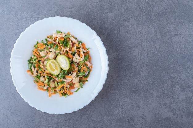 Salade de légumes savoureuse sur plaque blanche.
