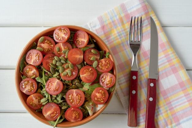 Salade de légumes à la tomate, laitue, graines de citrouille, dans un saladier.