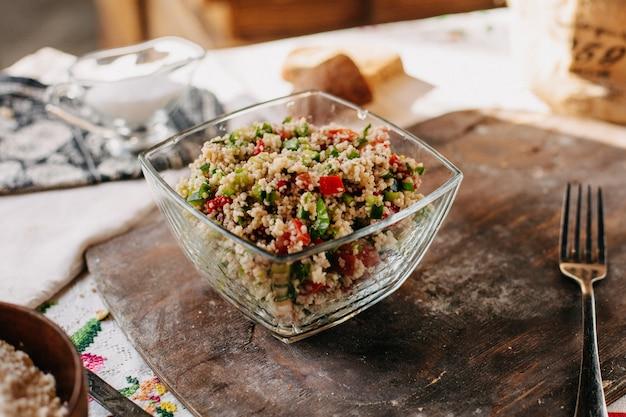 Salade de légumes en tranches peu de vitamines colorées en morceaux enrichies avec du riz salé poivré savoureux sur un bureau en bois brun
