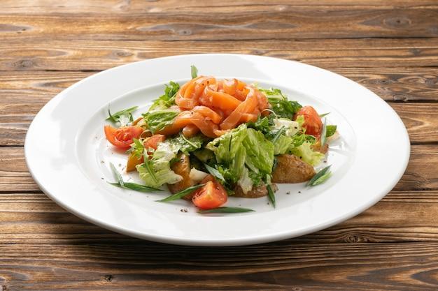 Salade de légumes végétarienne au saumon, pommes de terre et tomates cerises dans une assiette en céramique blanche