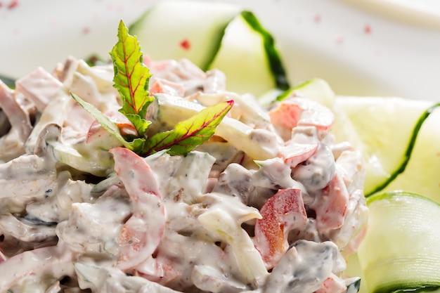 Salade de légumes avec de la viande et des herbes sur une plaque blanche