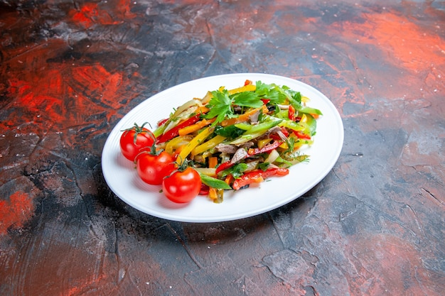 Salade de légumes vue de dessous sur une assiette ovale sur un espace libre de surface sombre