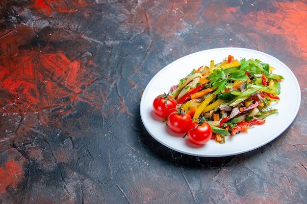 Salade de légumes vue de dessous sur une assiette ovale sur une surface rouge foncé avec lieu de copie