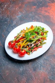 Salade de légumes vue de dessous sur une assiette ovale sur une surface sombre