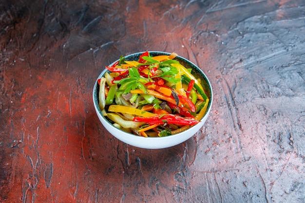 Salade de légumes vue de dessous dans un bol sur un espace libre de table rouge foncé