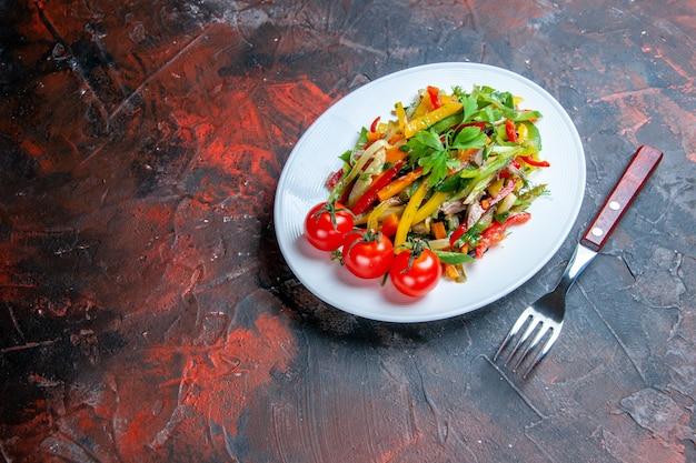 Salade de légumes vue de dessous sur une fourchette à assiette ovale sur un endroit libre de surface sombre