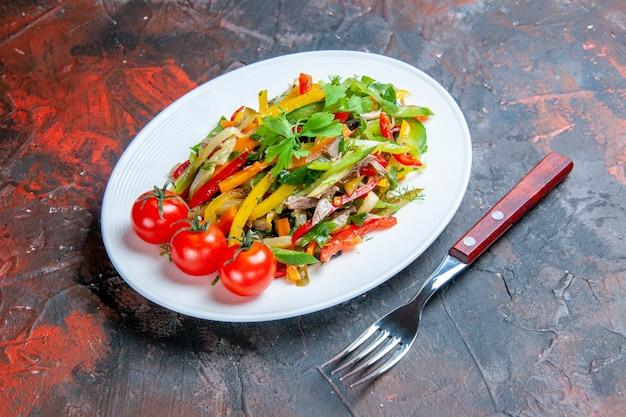 Salade de légumes vue de dessous sur une fourchette à assiette ovale sur une surface sombre