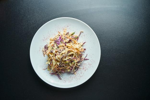 Salade lente végétarienne cole avec vinaigrette crémeuse, chou, carottes et épices sur une plaque blanche. vue de dessus