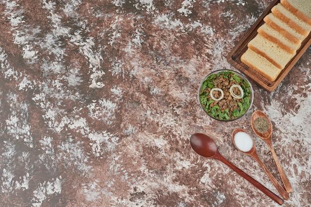 Salade de lentilles dans une tasse en verre avec des herbes et du pain.