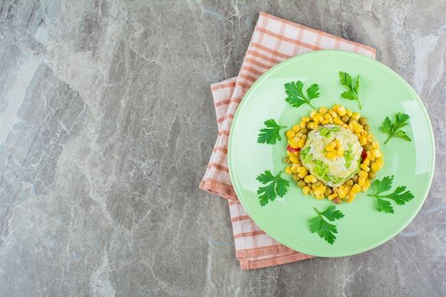 Salade de maïs sur une assiette sur un torchon, sur le marbre.