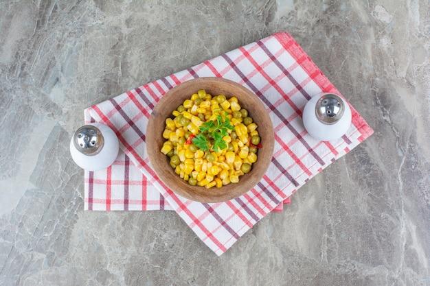 Salade de maïs dans un bol à côté de sel sur torchon sur marbre.
