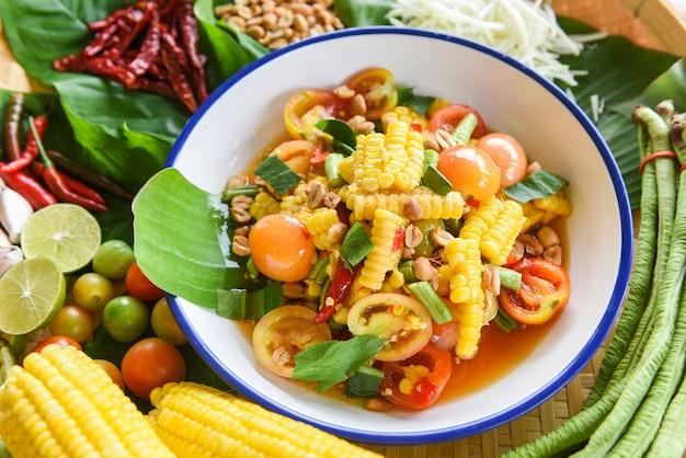 Salade de maïs épicée aux légumes frais, herbes et épices, ingrédients avec piment, tomate, arachide et ail