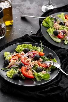 Salade maison à angle élevé avec vaisselle sombre