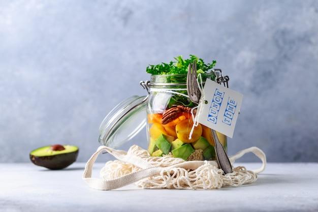 Salade maison dans un bocal en verre avec du quinoa et des légumes avec étiquette l'heure du déjeuner sans plastique et concept à emporter