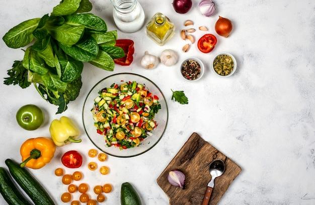 Salade maison de divers légumes biologiques dans un bol en verre avec des ingrédients et des épices