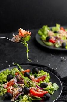 Salade maison avec vaisselle sombre