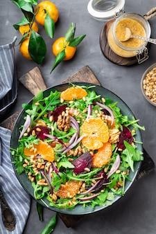 Salade de mandarine et de betterave fraîche faite maison avec des noix de roquette et des pignons de pin sur fond de béton