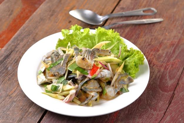 Salade de mangue épicée au crabe bleu sur une table en bois.