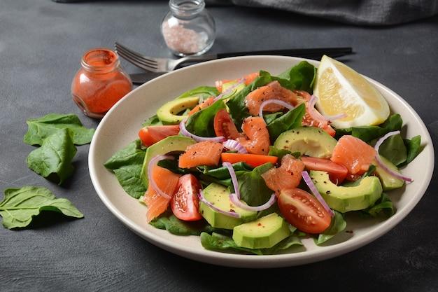 Salade méditerranéenne de saumon à l'avocat avec épinards, tomates cerises, avocat et vinaigrette à l'oignon rouge