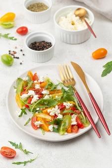 Salade de mélange de tomates à angle élevé avec fromage feta, roquette et couverts