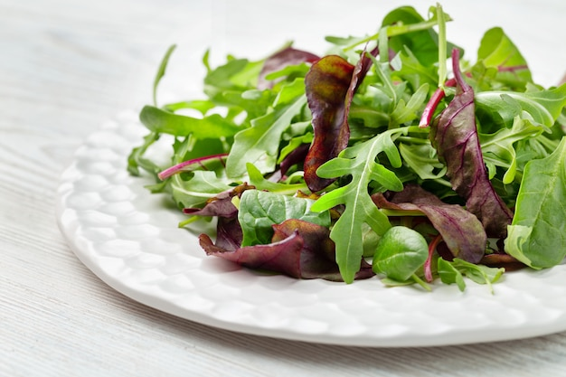 Salade - mélanger la salade verte et violette fraîche sur une plaque blanche