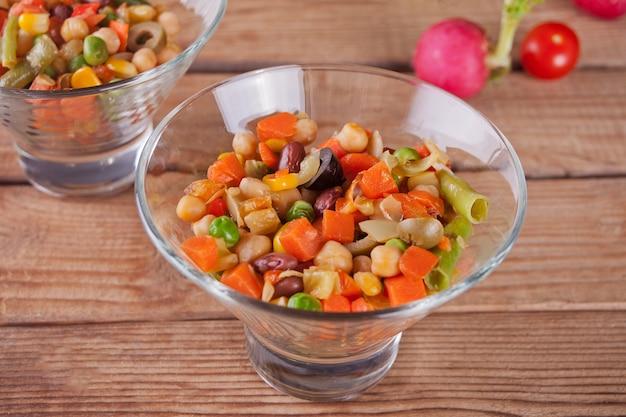 Salade mexicaine faite maison dans des bols avec haricots, maïs, tomates, poivrons et autres légumes.