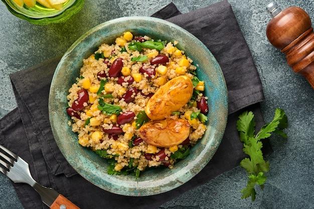 Salade mexicaine de quinoa de maïs aux haricots noirs avec du citron caramélisé dans un vieux bol d'argile vintage sur un fond de béton gris foncé. plat de cuisine traditionnelle mexicaine. vue de dessus, maquette.