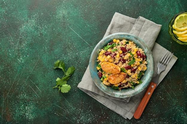 Salade mexicaine de quinoa de maïs aux haricots noirs avec du citron caramélisé dans un vieux bol d'argile vintage sur un fond de béton vert foncé. plat de cuisine traditionnelle mexicaine. vue de dessus, maquette.