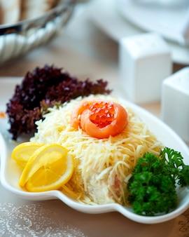 Salade de mimosa servie avec légumes verts, tranches de citron, caviar et tranche de saumon