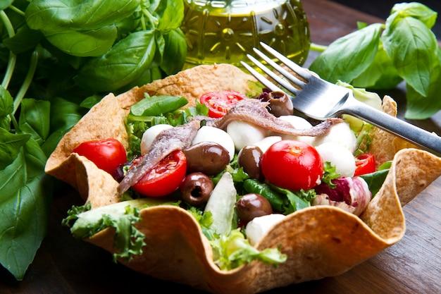Salade mixte avec mozzarella et anchois dans une corbeille à pain