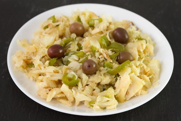 Salade de morue et de légumes sur une plaque blanche