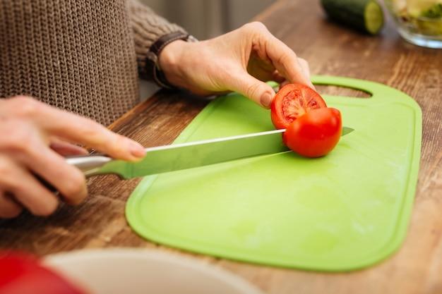 Salade nature. dame adulte préparant le dîner en utilisant des légumes frais tout en les coupant sur une table en bois