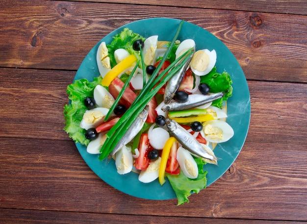 Salade niçoise aux anchois composée de salade de tomates, thon, œufs durs, olives niçoises et anchois, assaisonnée d'une vinaigrette