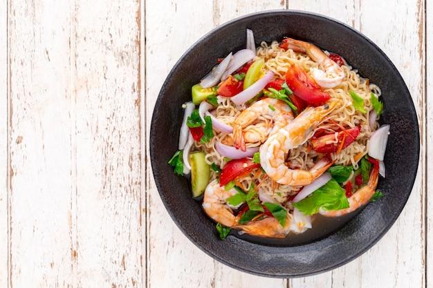 Salade de nouilles instantanées épicées et aigres aux crevettes, porc émincé, tomate, citron vert, oignon rouge, échalote et céleri dans une assiette en céramique noire sur fond de texture bois vieux blanc, vue de dessus, cuisine thaïlandaise, yum mama