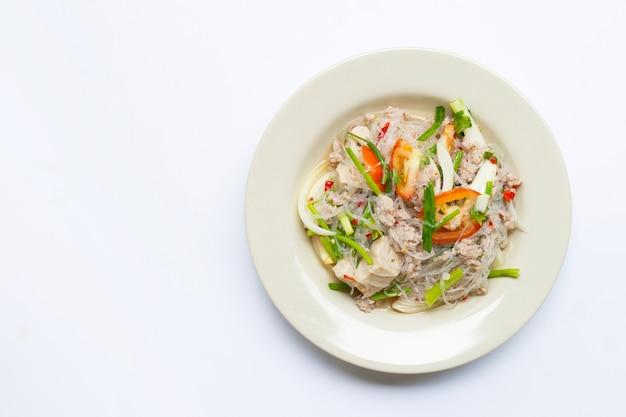 Salade de nouilles en verre épicé avec du porc isolé