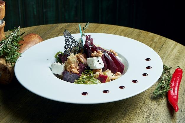 Salade nutritive et saine avec betteraves cuites au four, laitue, fromage feta, noix dans une assiette blanche. plat végétarien. gros plan sur une cuisine savoureuse. mise au point sélective