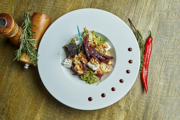 Salade nutritive et saine avec betteraves cuites au four, laitue, fromage feta, noix dans une assiette blanche. plat végétarien. vue de dessus avec espace copie