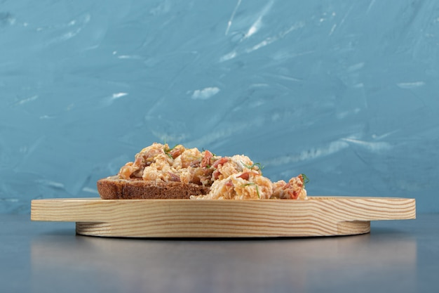 Salade d'oeufs et pain sur plaque de bois.