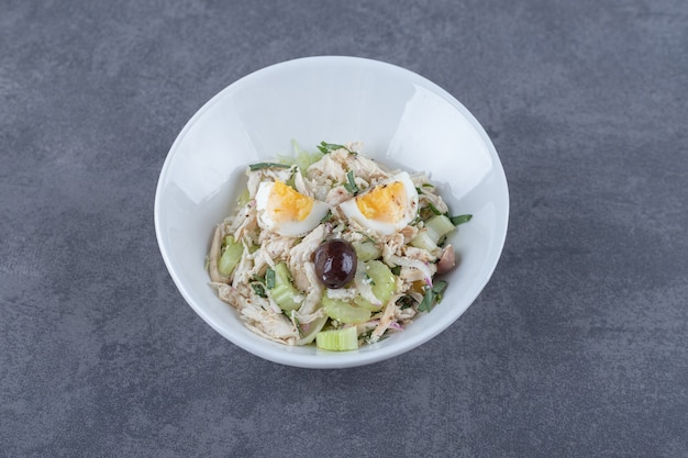 Salade d'œufs et de poulet en dés dans un bol blanc.