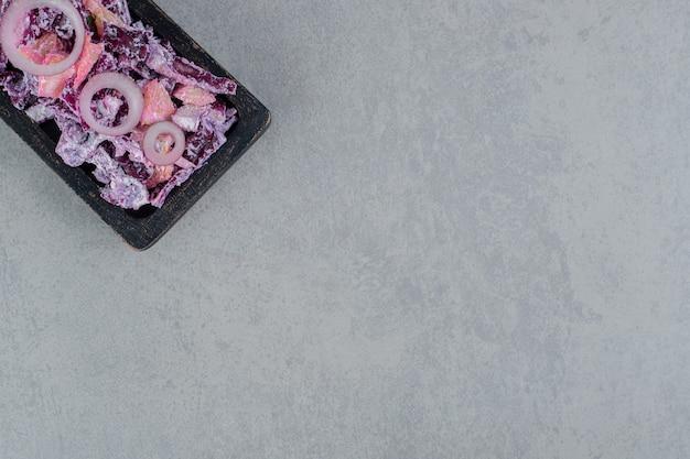 Salade d'oignons violets sur une planche carrée